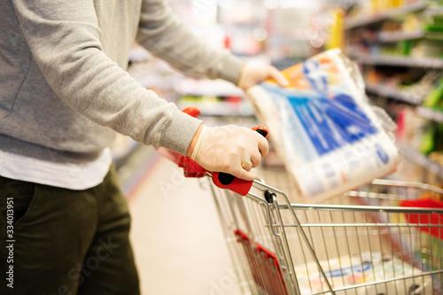Fotografie, Obraz Mann legt eine Packung Toilettenpapier in seinen Einkaufswagen