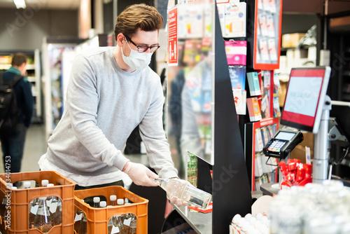 Schutz vor einer Ansteckung mit dem Coronavirus für die Kassierer im Supermarkt