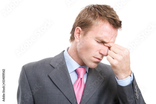 Photo Stressed businessman pinching the bridge of his nose to alleviate his headache w