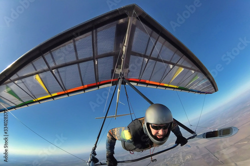 Fototapeta Hang glider pilot with his colorful wing flies high far away from other people