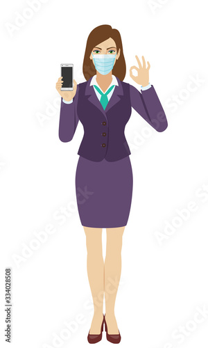 Businesswoman with medical mask holding a mobile phone and  show a okay hand sign Canvas Print