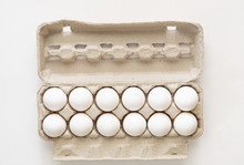 A Dozen Eggs In A Carton Isolated On White Background