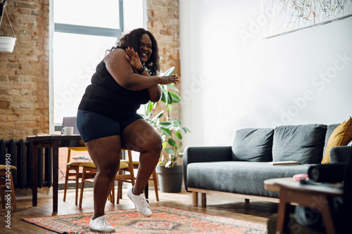 Carta da parati Positive plus size woman dancing at home stock photo