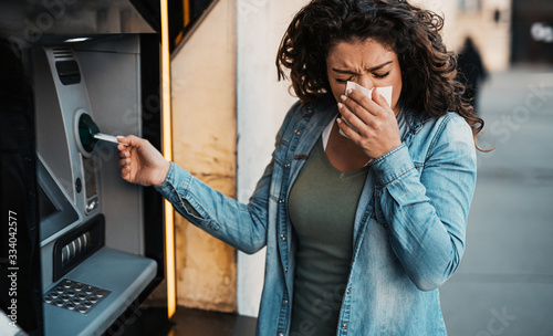 Fototapeta Young woman coughing and sneezing while using ATM machine to withdraw cash
