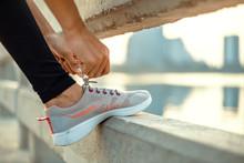 Woman Tying Shoe Laces.