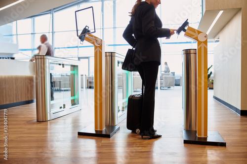 Photo Elegant lady passing electronic turnstile at airport