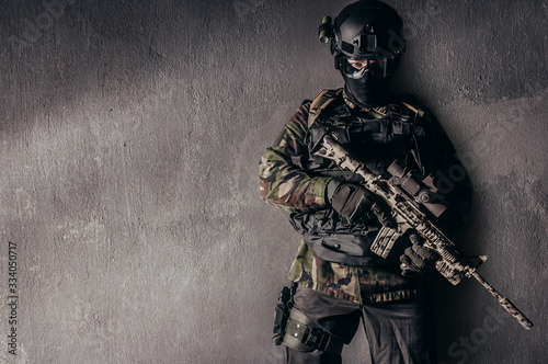 Fully equipped soldier standing on concrete wall background. Canvas Print