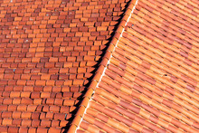Elevated View Of Classic Red Tile Clay Roof With Ridge Tile. One Cracked Tile Is Visible.