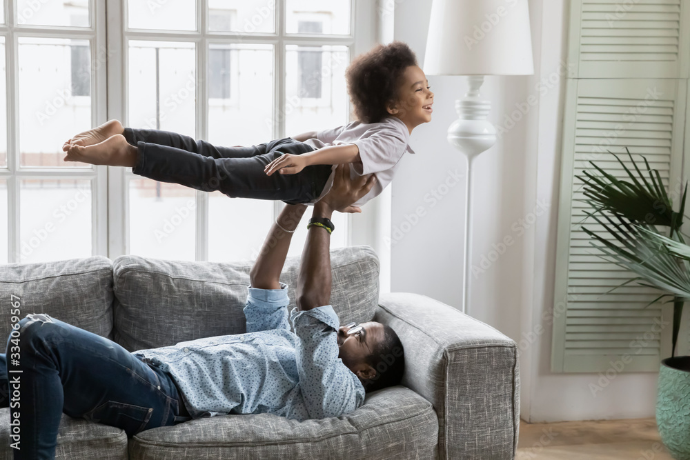 Fototapeta Mixed race African family spend time together in living room father lying on couch lift up son, little kid imitates plane imagines himself like flying in air. Funny activity on weekend at home concept