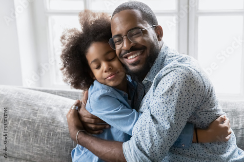 Photo Loving African father in glasses hugs little daughter, family sitting on couch c