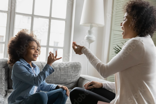 African disabled daughter and her mother sitting on sofa show symbols with hands using visual-manual finger gestures interacting at home. Hearing loss deaf person sign language learning school concept