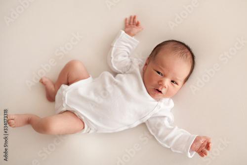 Cuadros en Lienzo Newborn baby boy in white body on bed