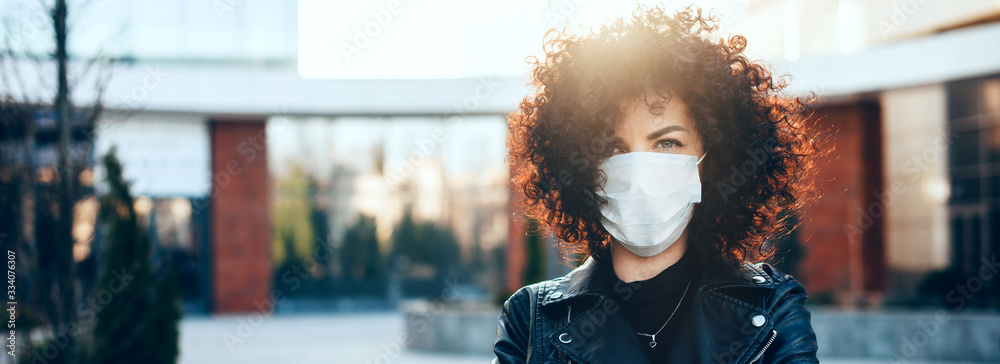 Fototapeta Protected caucasian woman with curly hair is posing in a sunny day while looking at camera and wearing a special white mask