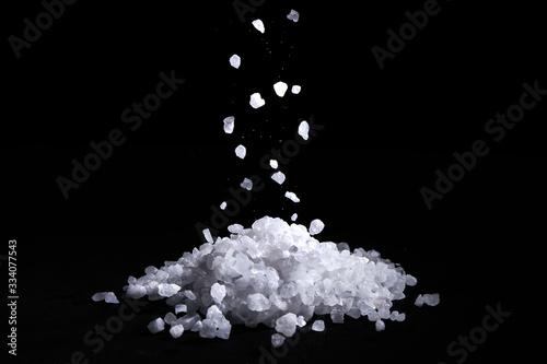 Foto Sea salt crystals fall on a pile of salt, black background