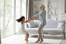 Overjoyed Senior Grandmother Dancing Entertaining With Little Granddaughter In Living Room, Happy Grandparent Have Fun Engaged In Funny Family Activity With Small Grandchild At Home Together