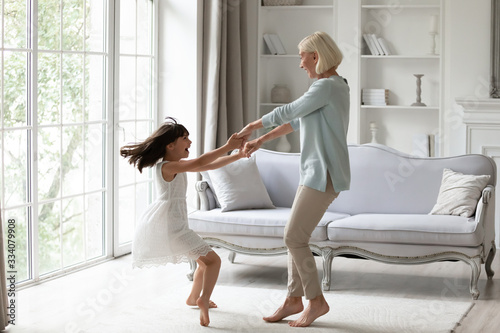 Obraz Overjoyed senior grandmother dancing entertaining with little granddaughter in living room, happy grandparent have fun engaged in funny family activity with small grandchild at home together - fototapety do salonu