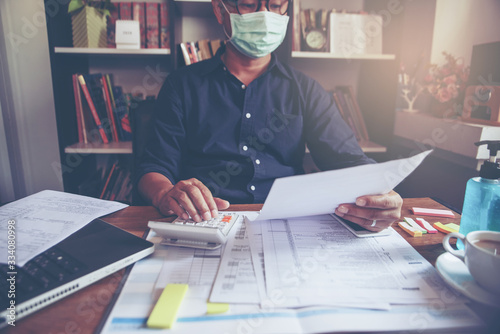 Fototapeta Budget planning concept, Accountant wear mask is calculating the company's annual tax. Calendar 2019 and personal income tax forms for those who have income under US law placed on home desk. obraz
