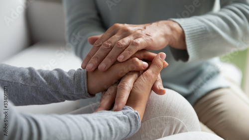 Fotografering Close up of mature mother and grown-up daughter sit on couch holding hands share