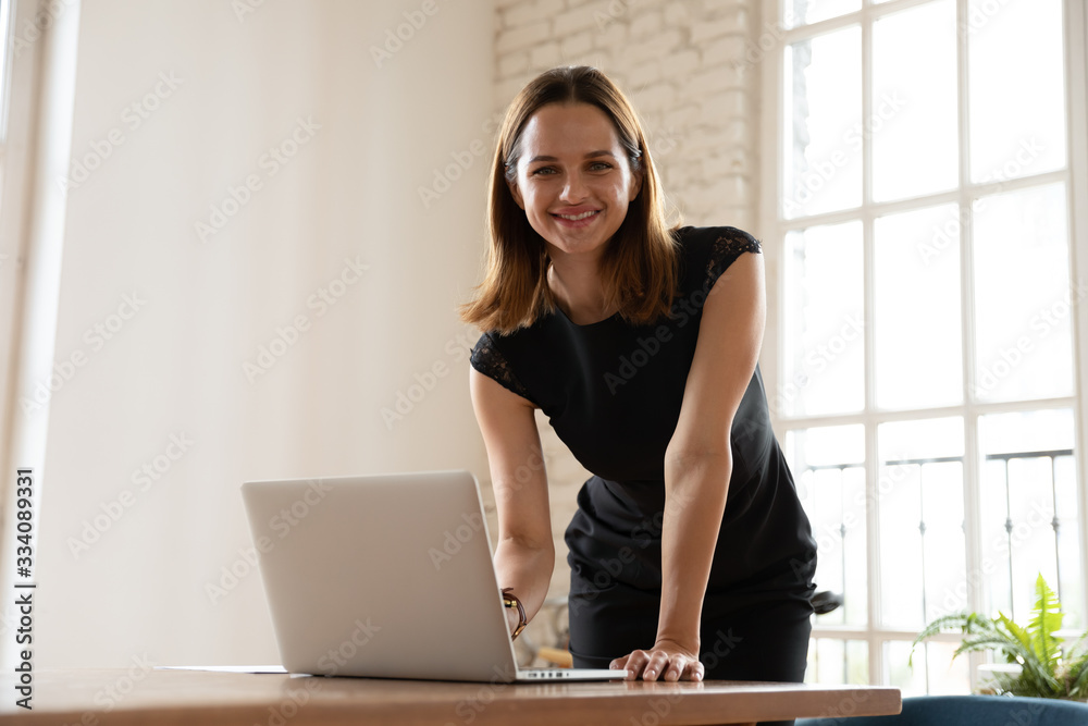 Fototapeta Confident female executive manager leaning over desk was distracted from working typing on laptop smiling looking at camera. Portrait of successful businesswoman, hired employee company representative