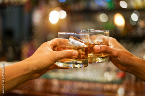 Two men clinking glasses of whiskey drink alcohol beverage together at counter i Wallpaper Mural