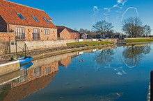 Houses And Boat Next To A River With Reflection