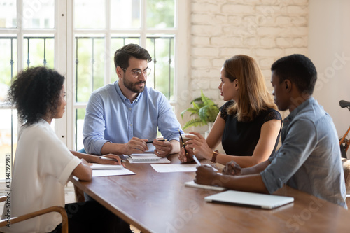 Photo Four diverse business partners negotiating in boardroom