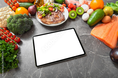 Fototapeta Tablet computer with white empty screen on a kitchen table surrounded by healthy products obraz