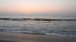 The sun over sea. Amazing red sunrise on beach palms island. Orange colors sunrise and waves. Nature sun sunrise palms beach background. Yellow sky, beautiful palm trees on the beach isle. Sunshine. A