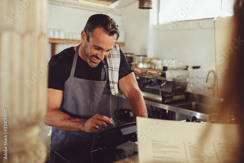 Barista entering customer order in cashbox computer Canvas Print