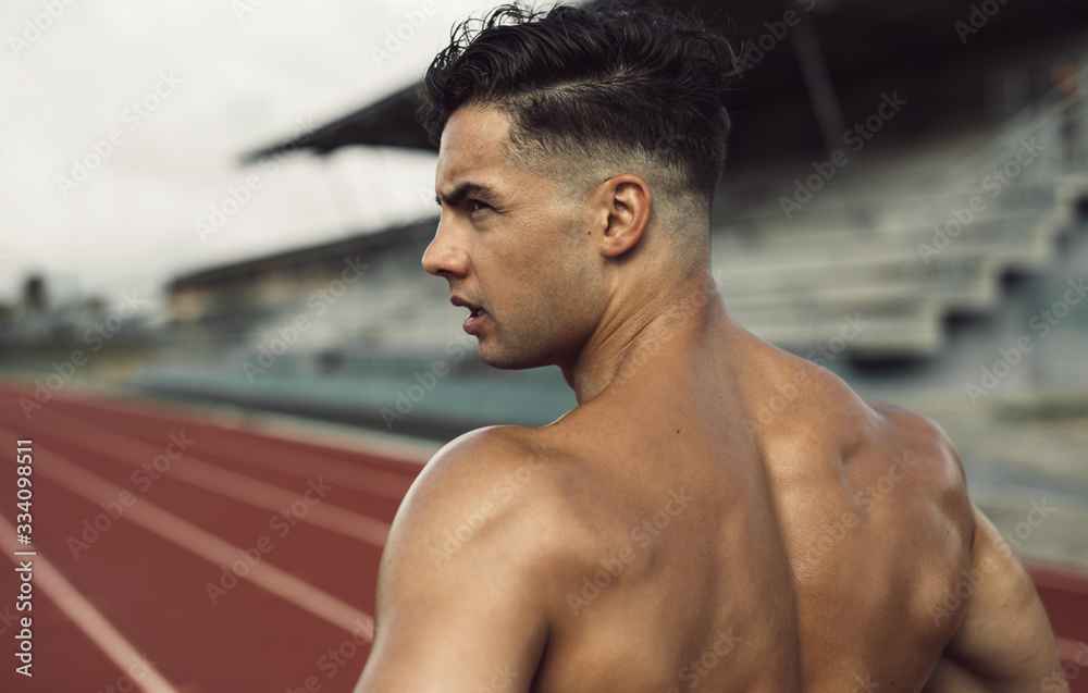 Fototapeta Healthy young man standing on track field