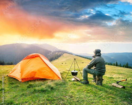 Fotomural Male tourist is sitting on log near orange tent in mountains