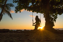 Silhouette Of A Girl Sitting On A Swing At Sunset By The Sea, Koh Chang Island, Thailand