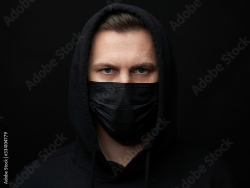 Fotografia Young man wearing face mask over black background, close-up