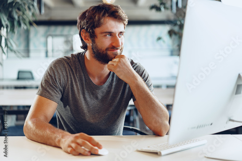 Obraz Bearded man freelancer using computer in a modern coworking place. Freelance business concept - fototapety do salonu