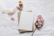 Wedding Stationery Mock-up Scene. Blank Vertical Greeting Card, Envelope On Linen Tablecloth Background With Pink Blossoming Cherry Tree Branches And Ribbon. Feminine Still Life Composition. Flat Lay.
