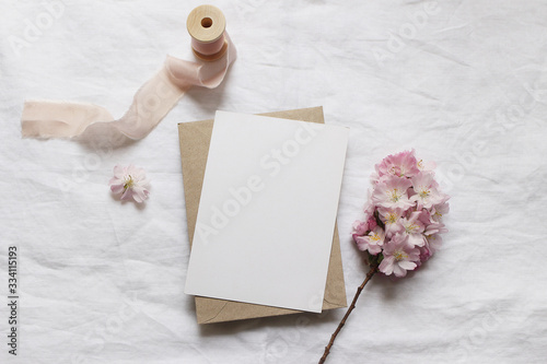 Fototapeta Wedding stationery mock-up scene. Blank vertical greeting card, envelope on linen tablecloth background with pink blossoming cherry tree branches and ribbon. Feminine still life composition. Flat lay. obraz