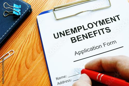 Fototapeta Man fills in Unemployment benefits application form. obraz