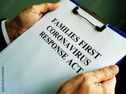 Photo Businessman reads families first coronavirus response act FFCRA.