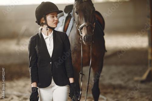 Fototapeta Woman near horse. Rider in a black uniform obraz