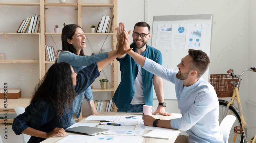 Fototapeta Overjoyed diverse businesspeople gather in office gave high five celebrate shared victory or win, happy multiracial colleagues coworkers join hands engaged in teambuilding activity at meeting