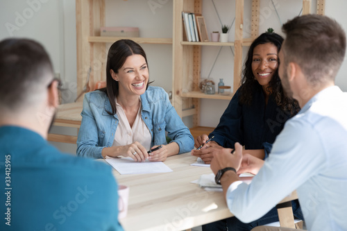 Fototapety, obrazy: Happy diverse colleagues coworkers sit at desk in office have fun discussing ideas at briefing together, smiling multiracial businesspeople laugh and joke brainstorming cooperating at team meeting