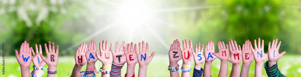 Fototapeta Children Hands Building Colorful German Word Wir Halten Zusammen Means Together We Are Stron. Sunny Green Grass Meadow As Background