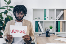 African American Employee Showing Placard With Unemployed Lettering In Office