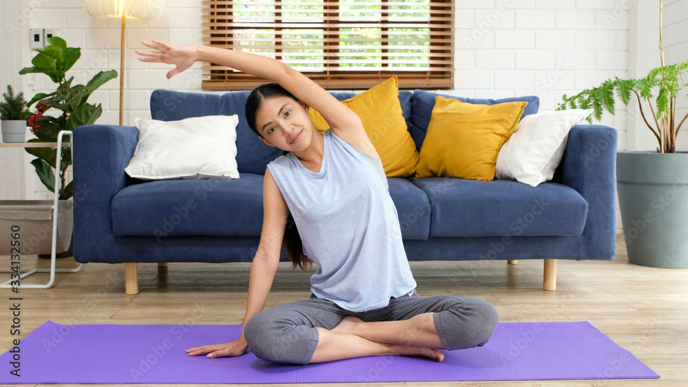 Fototapeta Exercise at home, social distancing, Asian girl body stretch for workout fitness, Healthy asia woman exercising in home living room, Quarantine female people do yoga for relax, wellness, well being,