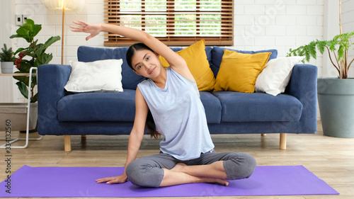 Fotografia Exercise at home, social distancing, Asian girl body stretch for workout fitness