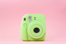 Green Instant Camera On A Pink...