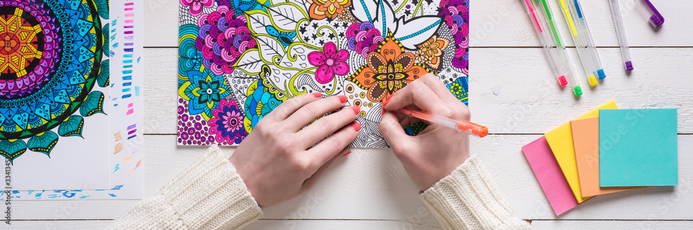 Fototapeta Adult coloring book, stress relieving trend. Art therapy, mental health, creativity and mindfulness concept. Flat lay close up on woman hands coloring an adult coloring book web banner.