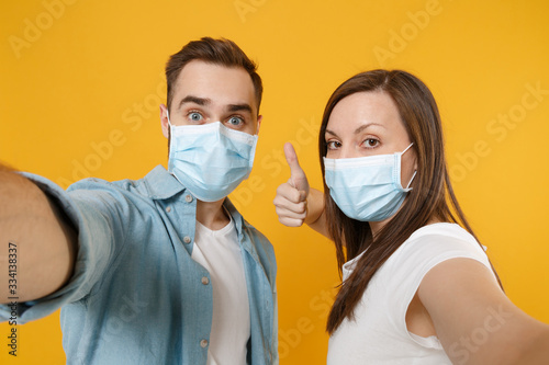 Fototapety, obrazy: Two people in sterile face masks white t-shirts isolated on yellow background studio. Epidemic pandemic rapidly spreading coronavirus 2019-ncov medicine flu virus ill sick disease treatment concept.
