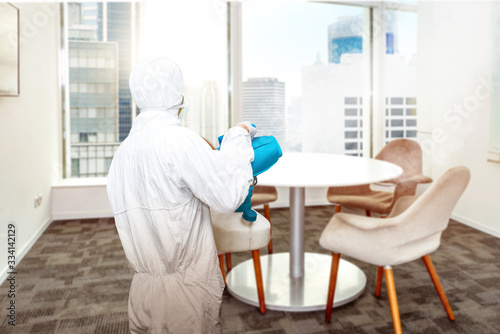 Leinwand Poster Man in a white protective suit spraying disinfectant in the office room