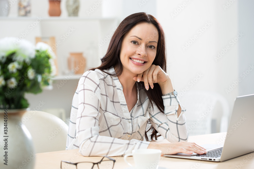 Fototapeta Portrait of business woman looking at camera at workplace in a home office